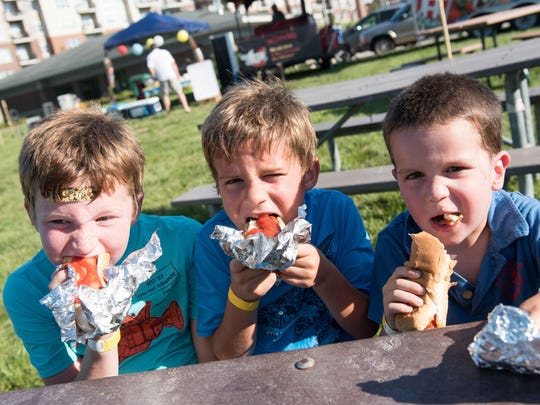 Aidan, 8, Dylan, 6, and Derek, 3, Ducharme enjoy hotdogs
