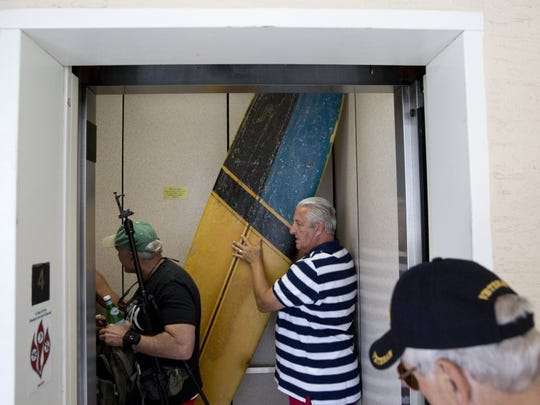 The four Marines load up to head to Cinnamon Beach as Bob Falk squeezes the surfboard, essential to the recreation of the photo, onto the elevator Saturday, April 23, 2016. The group hadn't all been in he same place since being shipped off to fight in the Vietnam War, nearly 50 years.