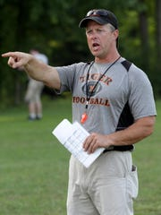 Middlebury Union High School football head coach Dennis Smith shouts instructions during evening varsity practice last week.