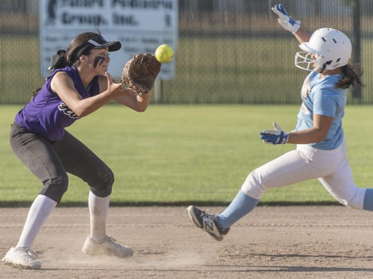 Mission Oak's Lauren Reynoso waits on a throw as she eyes Monache's Jessenia Castillo sliding to second in an East Yosemite League high school girls softball on Tuesday, May 2, 2017.