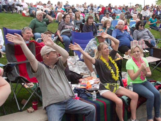Audience members sway to the music of Air Margaritaville performing at the historic County Courthouse amphitheater during the Howell Melon Festival Friday, Aug. 18, 2017.
