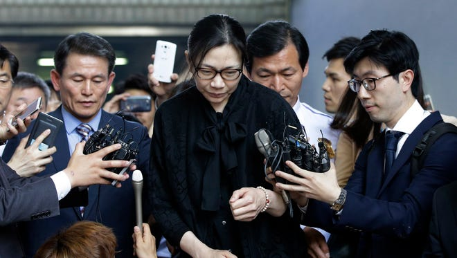 In this May 22, 2015, file photo, former Korean Air executive Cho Hyun-ah, center, is surrounded by reporters as she leaves the Seoul High Court in Seoul, South Korea.