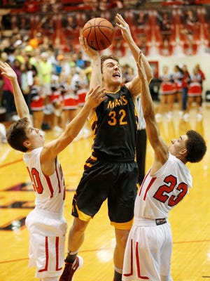 McCutcheon's Haden Deaton drives between Danny Isbell, left, and Darian Collins of Lafayette Jeff for a shot Thursday, February 4, 2016, at Crawley Center. McCutcheon avenged a loss to Jeff in the championship of the J&C Hoops Classic with a 59-43 victory.