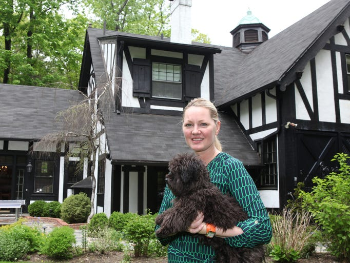 Cami Fischer holds her dog Wolfie outside her home that was the former Julliard family carriage house, an historic property in Tuxedo Park.
