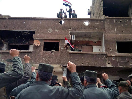 In this photo released by the Syrian official news agency, SANA, Syrian military and police forces fly their national flags on a damaged building in the Hajar al-Aswad neighborhood, southern Damascus, Syria, May 22, 2018. Syrian state TV said Tuesday the military and police forces are celebrating recapturing the last neighborhoods in Damascus that were held by the rebels and the Islamic State group.
