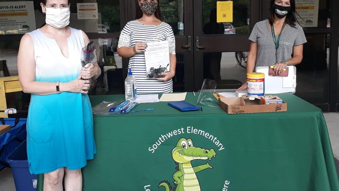 Southwest Elementary School fifth-grade teacher Rebecca Scott, left; fourth-grade teacher Emma Ruby, and principal Tara Fitzgerald distributed Chromebooks to parents who had signed up to receive them on Aug. 15.
