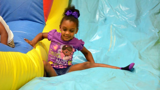 """Brooklyn Spencer, 5, plays on an air slide Friday on the final full day of the city of Alexandria's Summer Camp. A speaker at the city's Recreation Summit said the $10-a-week fee for the camp was """"an unbelievable deal."""""""