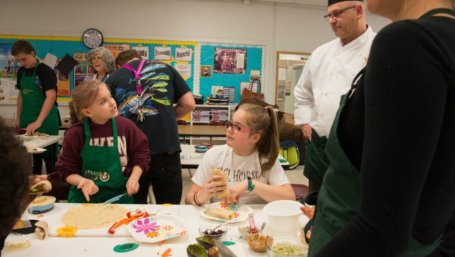 Taylor McKee, left, asks chef Jeff Sparicino questions about her veggie wrap at the Green Aprons Club two weeks ago.