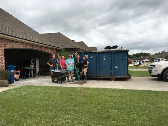 Staff, parents and students from L. Leo Judice Elementary are helping school librarian Lisa Labarraque begin to restore her flooded home.