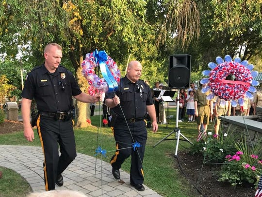 Little Falls Police Chief Steven Post, left, and Sgt. Jim Minnella carry a wreath to be placed in front of a 9/11 memorial in Wilmore Road Park. The 9/11 remembrance ceremony was held on Sept. 11, 2017 to mark the 16th anniversary of 9/11.