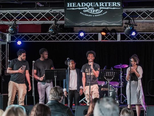 Members of Fenix Youth Project Inc. perform poetry onstage at Headquarters Live in Salisbury.