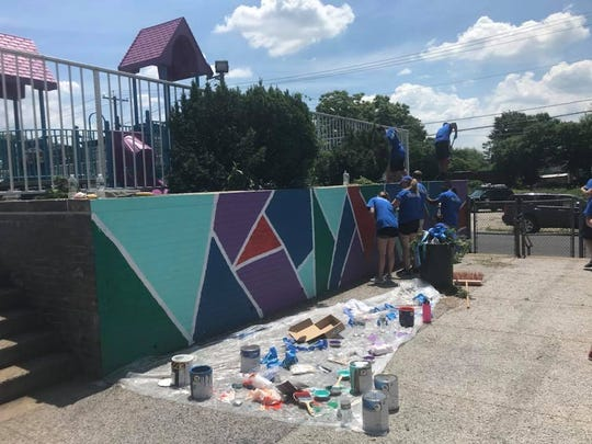Volunteers paint outside the playground of U.S Wiggins Family School in Camden on Friday.