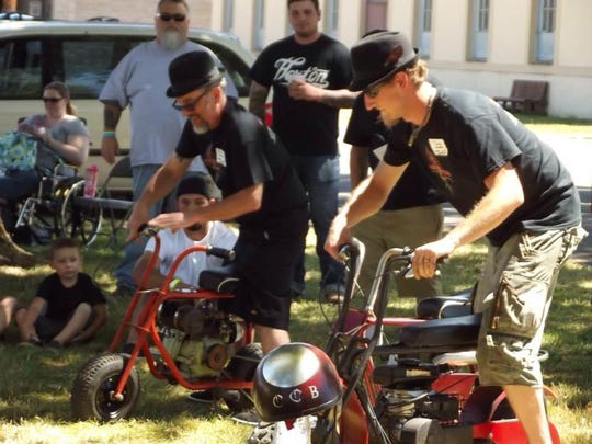 Members of the Cherry City Bombers car club compete in the mini motorbike race.