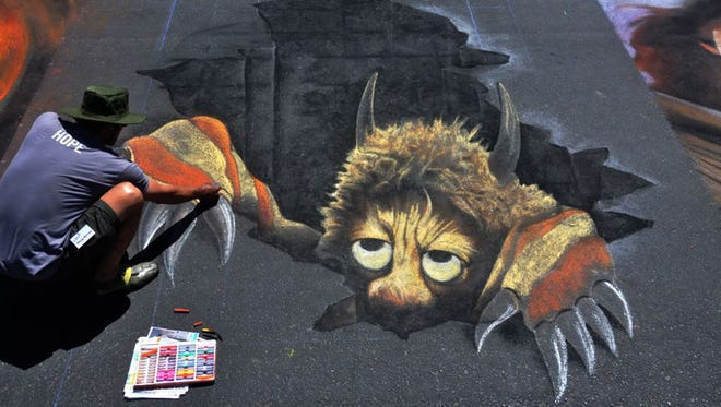 Douglas Rouse puts the finishing touches on his piece during the 2011 Chalk It Up! event in Prescott.