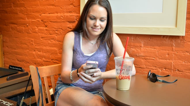 Angelique Quintana, 28, of Colchester checks out her Facebook app on her iPhone at Bruegger's Bagels in Burlington on July 22.