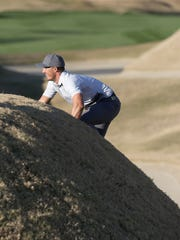 Jamie Lovemark climbs out of a very deep bunker on