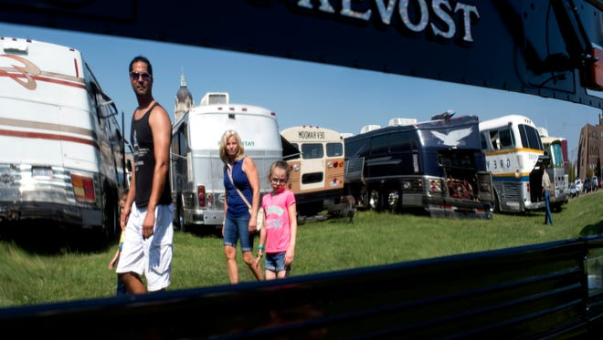 From right to left: Ava Ashworth, 7, Teresa Anoskey, Tom Bergman, and Eli Ashworth, 5, are reflected in a 1985 Prevost bus at the Bus Boys' Vintage Bus Rally at Bru Burger in downtown Evansville, Ind., on Saturday, Sept. 23, 2017. The weekend event included bus rides, a live auction, and food vendors.