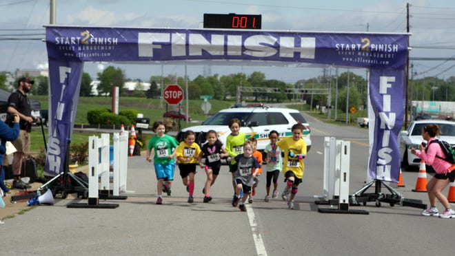 Runners cross the finish line in the Du The Dream duathlon, a fundraiser for Dream Factory Inc., on Saturday.