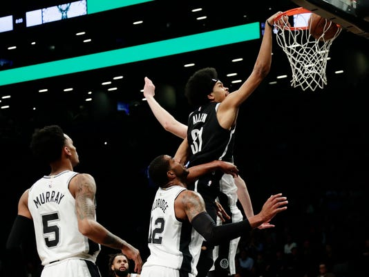 Brooklyn Nets' Jarrett Allen (31) dunks the ball in front of San Antonio Spurs' LaMarcus Aldridge (12) and Dejounte Murray (5) during the first half of an NBA basketball game Wednesday, Jan. 17, 2018, in New York. (AP Photo/Frank Franklin II)