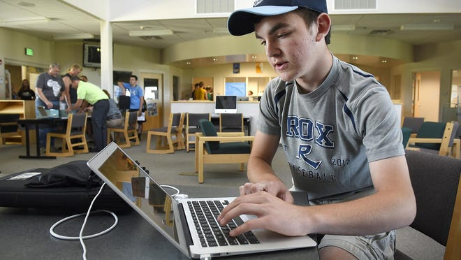 Sauk Rapids-Rice High School senior David Hoeschen logs into his new MacBook Air computer after picking it up Tuesday, August 11 at the school. All Sauk Rapids-Rice high school students are getting computers to use for the school year.