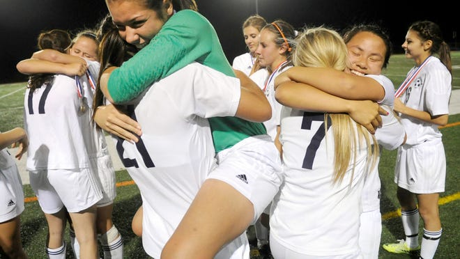 Dallastown celebrates on the sidelines after they received their medal for winning Friday night's final match in the YAIAA soccer tournament at Northeastern.