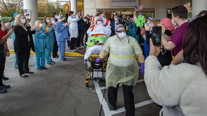 As health care workers cheer her on, Kim Dobson, center, 63, of Burlington City, is released from Virtua Memorial in Mount Holly on Monday.