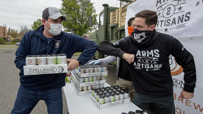 Michael Shepard, left, of the Eastampton FOP, elbow bumps, Jason Carty, of Lumberton, a board member of nonprofit Arms 2 Artisans, as he accepts a free case of beer for his members Wednesday.