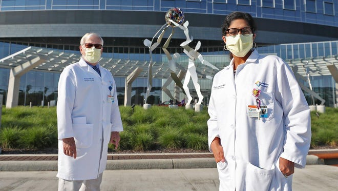 "Dr. Thomas File, chairman of the Infectious Disease Division at Summa Health, and Dr. Shanu Agarwal, Summa Health infectious disease physician, stand near the ""Beacon of Well-Being"" sculpture Thursday at the Summa campus."
