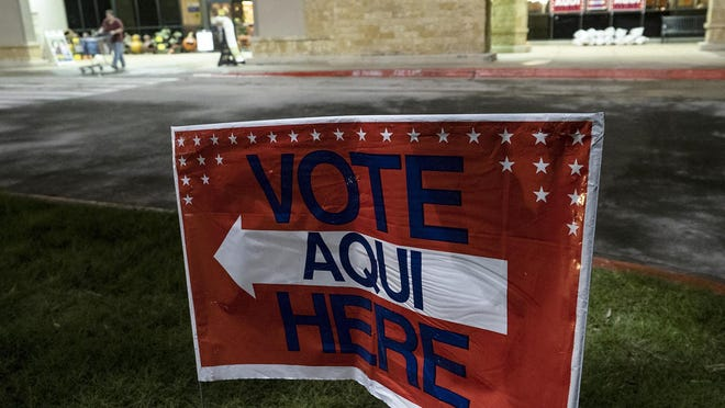 A sign directs voters to the entrance of an early voting site outside a Randalls grocery store in Austin.