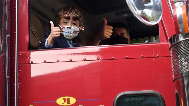 Grayson Sillanpaa, 5, and Abe McGuire give thumbs up as they prepare to drive to the courthouse where Grayson is being adopted by the Silanpaa family Wednesday morning. Grayson's only wish was that he could ride there in a dump truck.
