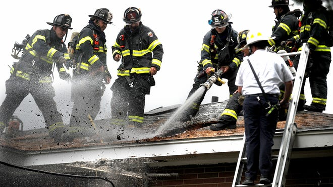 Firefighters extinguish a fire in an attic space on Second Street in Framingham on Monday afternoon.