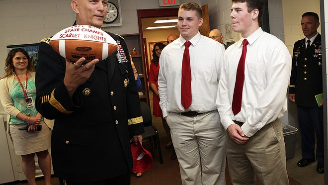Gen. Raymond T. Odierno, Army chief of staff, with football players Ryan Jackson, and Kevin Cassidy at Morris Hills High School.