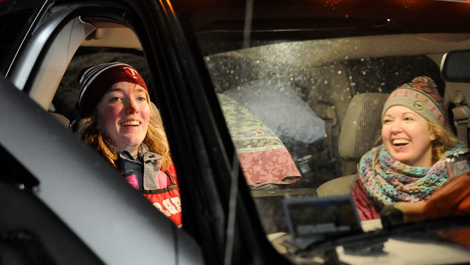 Musher Kayla Borntrager, 16, Elk River, and her sister Jill Wagner sit in the truck and get warm after finishing the first leg of the John Beargrease Sled Dog Marathon mid-distance race Sunday night.