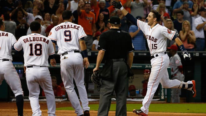 Jason Castro #15 of the Houston Astros (L) is greeted by his teammates after hitting a three-run home run in the ninth inning to end the game and defeat the Los Angeles Angels of Anaheim 3-0 during their game at Minute Maid Park on July 30, 2015 in Houston, Texas.
