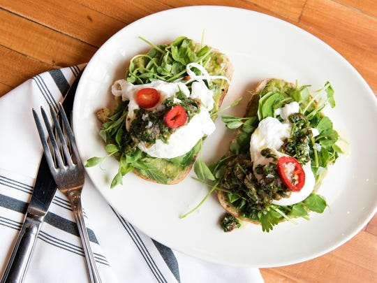 Avocado toast with poached egg, salsa verde, herb salad and chilis.
