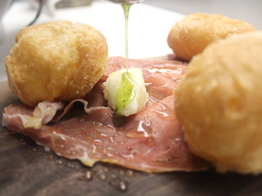 A Coccoli Platter includes light-as-air fried bread balls, prosciutto de parma, stracchino cheese, truffle honey and herb oil.