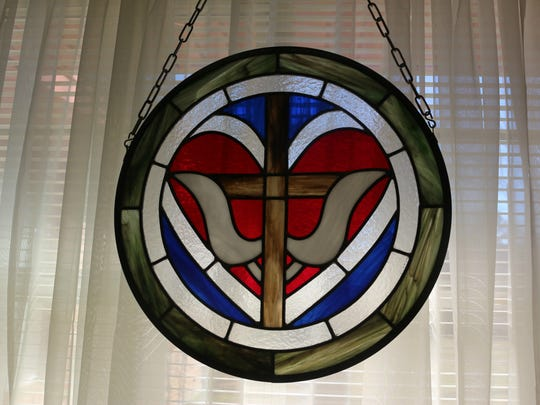 A stained glass replica of the Trinity Medallion.