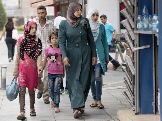 Syrian migrants walk near Basmane train station Saturday in the coastal city of Izmir, Turkey.