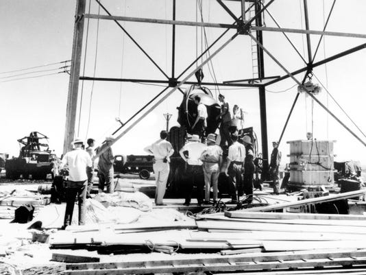 In this July 1945, photo, scientists and workmen rig the world's first atomic bomb to raise it up into a 100-foot tower at the Trinity bomb test site in the desert near Alamogordo.