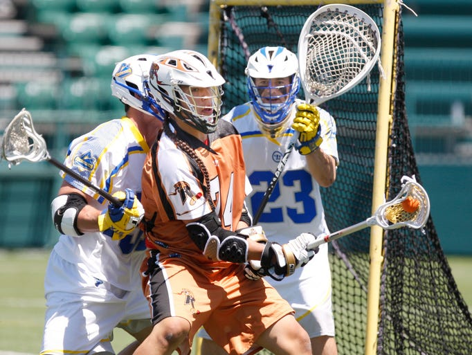 Rochester's Miles Thompson, 74, right, backs down Florida's Tucker Durkin, left, before spinning in for a shot on Florida goalie Brett Queener, 23, during their game Sunday, June 1, 2014 at Sahlen's Stadium in Rochester.