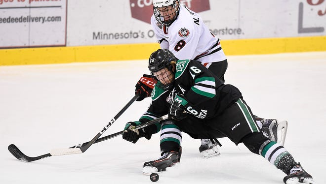 St. Cloud State's Nick Poehling, 8, and University of North Dakota's Brock Boeser get tangled chasing the puck during the first period Friday, Nov. 18, at the Herb Brooks National Hockey Center.