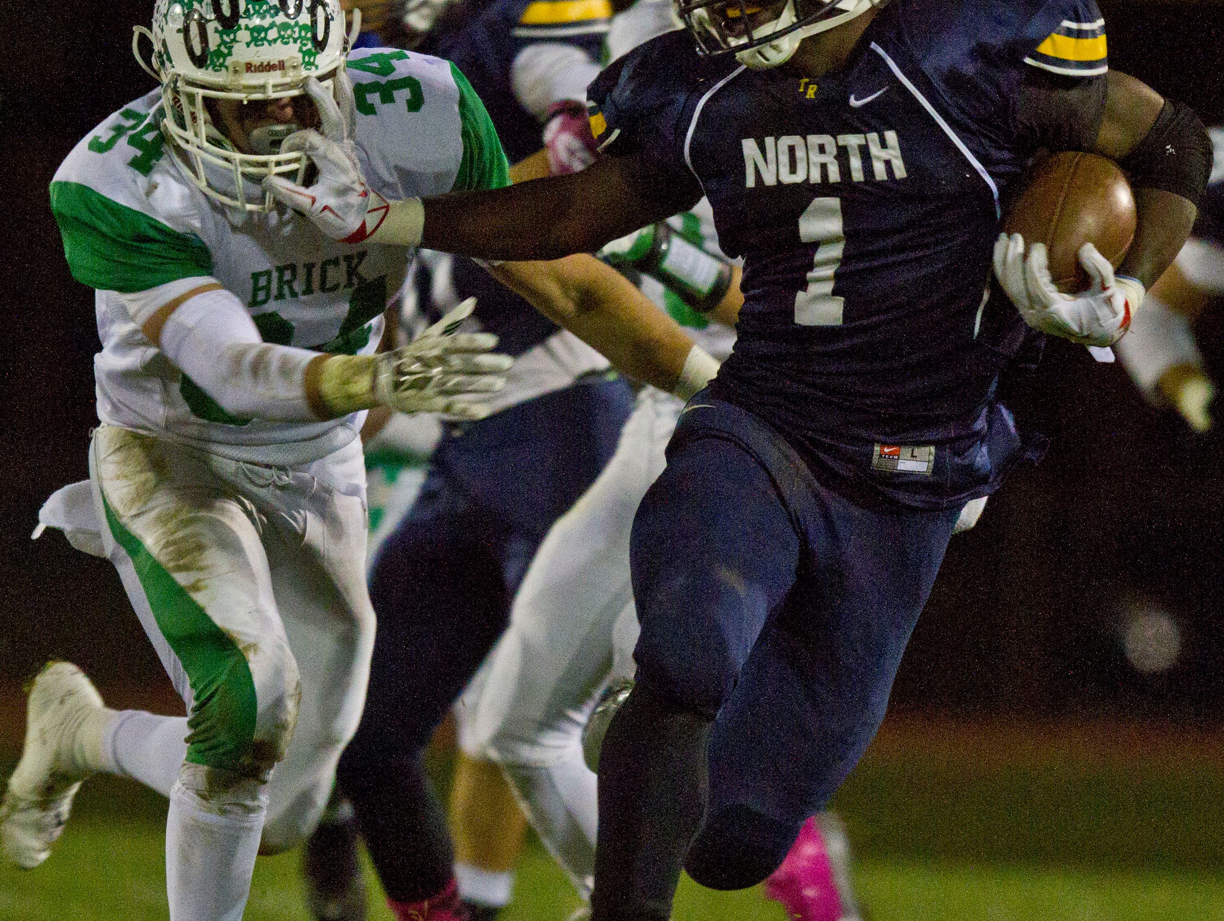 Toms River North's Asante Moorer (1) gains yards on the ground. Toms River North vs Brick football. Brick, NJ Friday, October 30, 2015 @dhoodhood
