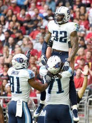 Titans running back Derrick Henry (22) celebrates his touchdown with tight end Jonnu Smith (81) and guard Dennis Kelly (71) during the first half Sunday.