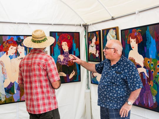 Mamuka Didebashvili, of Georgia, left, and Konstantin Dzamashvili, of Bonita Springs, look at art during the Bonita Springs National Art Festival on Saturday, Jan. 14, 2017.