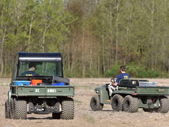 FBI agents from the Detroit Field Office cross a field