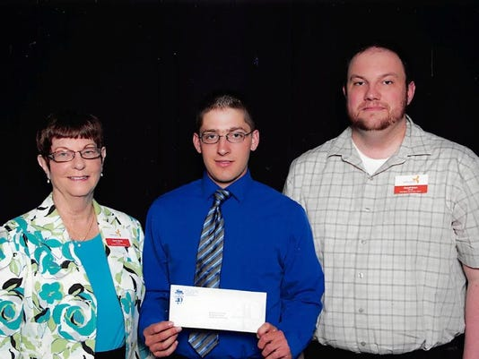 Sandra Abnett, left, president of the East Berlin Community Library Board of Trustees, presented the $500 scholarship check to Joshua Shank, center, with Brandt Ensor, director of the East Berlin Community Library, looking on.