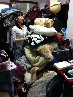 "Marie Kondo works at a client's home to clear away everything that is unneeded and fails to ""spark joy."" Kondo's method of decluttering is known as the KonMarie Method."