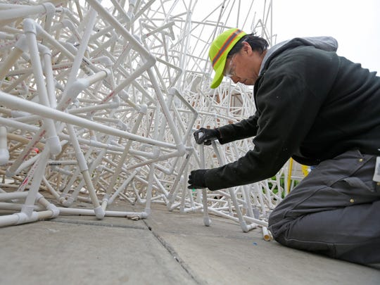"Artist Jason S. Yi, of Milwaukee, works on his sculpture titled ""The Legend of the White Snake"" consisting of PVC pipes. It's on the northeast corner of W. Wisconsin Avenue. and N. 6th St."