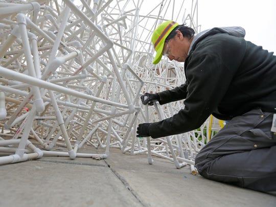 Artist Jason S. Yi, of Milwaukee, works on his sculpture