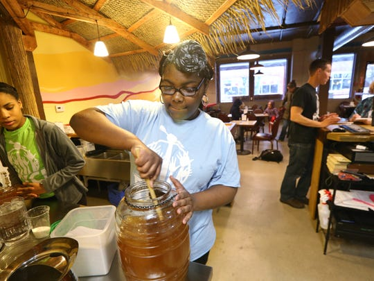 Claueshell Davidson, a senior at East High, mixes up a fresh batch of sweet tea at the newly opened Rochester Youth Culinary Experience in the Village Gate.
